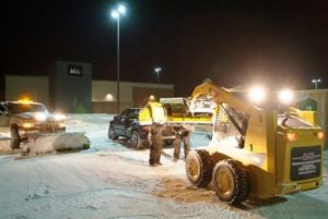 Snow removal trucks and team members in parking lot