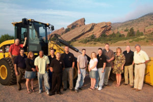 Photo of CAM Services staff in front of heavy machinery